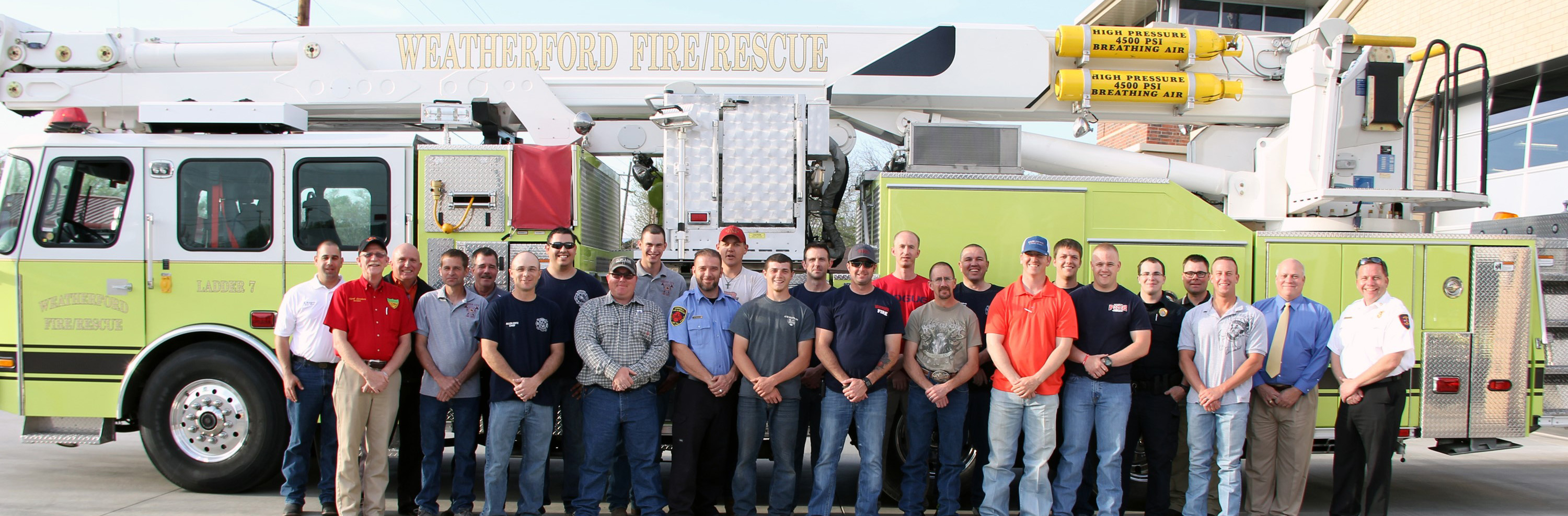 picture of the whole fire department in casual clothing by one of the fire trucks