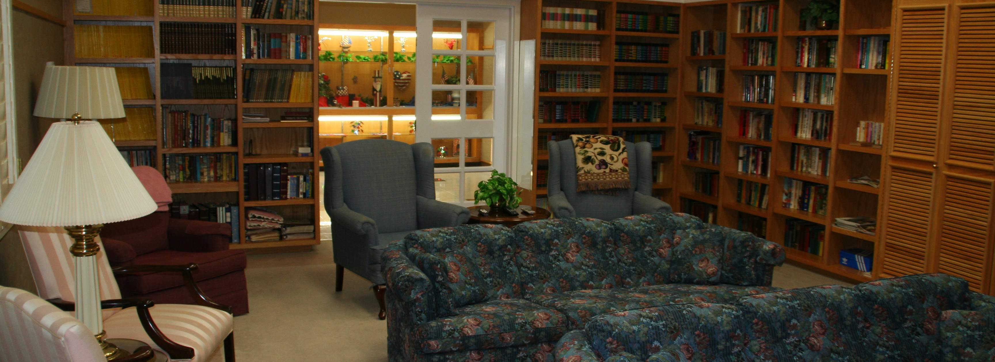 a picture of one of the sitting areas in the Pioneer Center. The area includes bookcases, a couch, and a couple of chairs